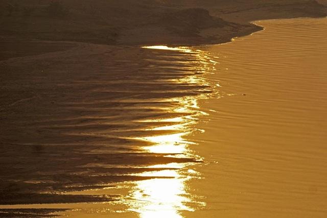 Bãi bồi ven sông cũng ngả sang màu vàng rực rỡ của ánh bình minh.