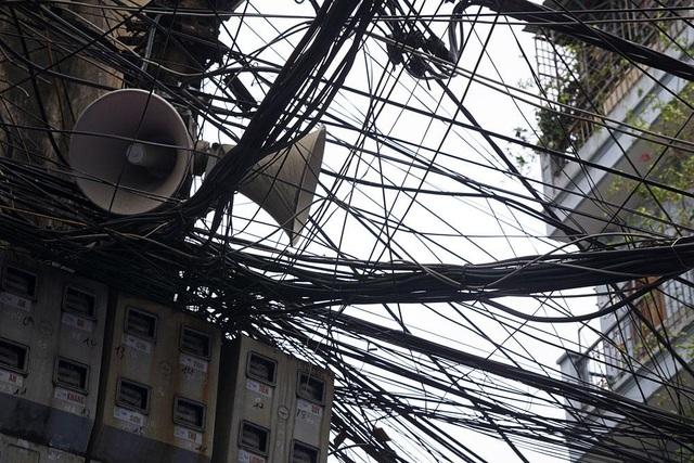 Loa phường thường được treo trên cột điện nhằng nhịt dây cáp. Trong ảnh là đôi loa giữa búi bùng nhùng tại ngõ Hội Vũ (quận Hoàn Kiếm).