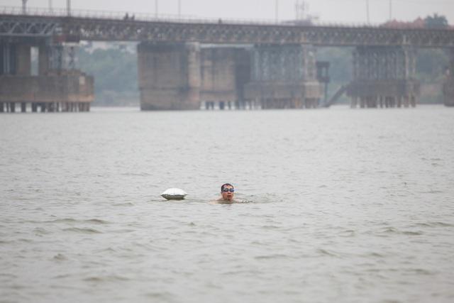 """Sau khi cùng các """"đồng môn"""" làm nóng cơ thể, ông Phúc bắt đầu thả mình vào dòng sông Hồng đỏ đặc phù sa. Để an toàn khi bơi, ông Phúc kéo theo quả bóng bay giấy kính làm phao."""