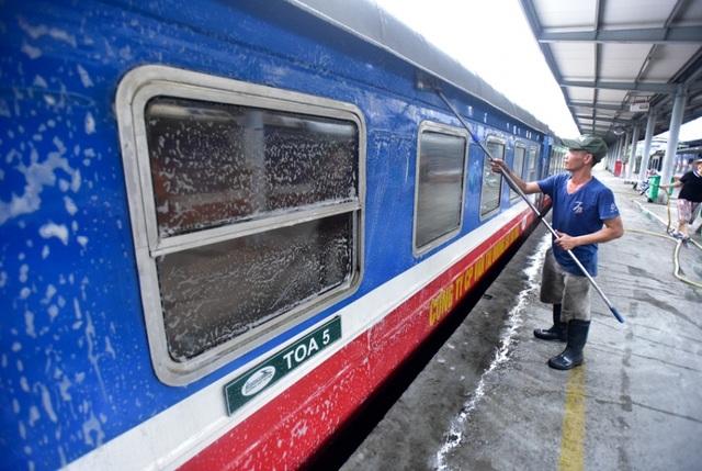 Nhân viên rửa các toa tàu của một đoàn tàu đang nằm trong nhà ga, trước khi tàu bắt đầu hành trình mới.
