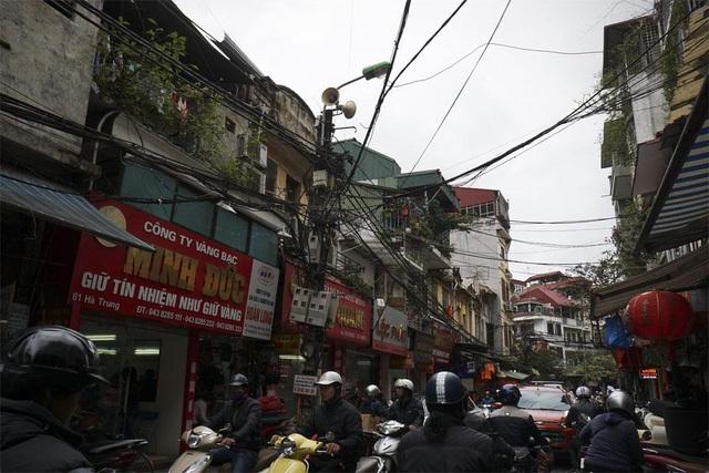 Hệ thống loa treo trên cột đèn với chiều cao ngang mái ngôi nhà 3 tầng trên phố Hà Trung (quận Hoàn Kiếm).