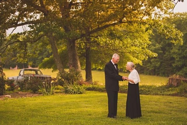 Cụ ông ân cần dắt tay cụ bà đi từng bước trên bãi cỏ xanh