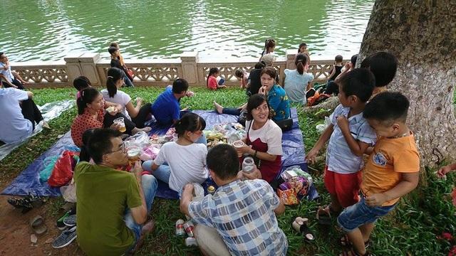 Nhiều gia đình chọn nơi có bóng mát và trải bạt trên thảm cỏ để ăn uống