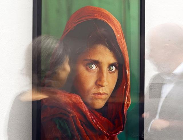 Một nhóm du khách bước qua bức ảnh nối tiếng Cô gái Afghanistan trong cuộc triển lãm của nghệ sĩ nhiếp ảnh trứ danh Steve McCurry tại Erfurt (Đức). Ảnh: AP