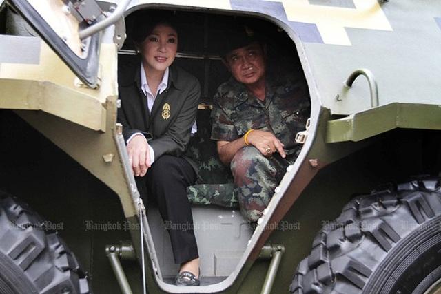 """Thủ tướng Yingluck và chỉ huy quân đội thời điểm đó – ông Prayut Chan-o-cha ngồi trong xe bọc thép quan sát cuộc diễn tập chung có tên """"Kotchasee 2012"""" của quân đội Thái Lan và Singapore ở Watthana Nakhon (Sa Kaeo, Thái Lan) ngày 6/4/2012. Ảnh: Bangkok Post"""