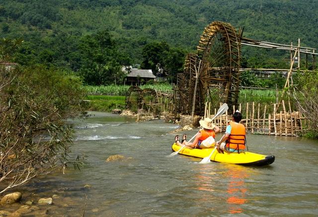 Du khách chèo thuyền trên suối.