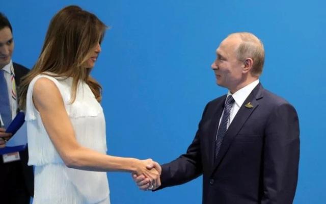 Tổng thống Putin bắt tay bà Melania Trump tại Đức (Ảnh: Reuters)