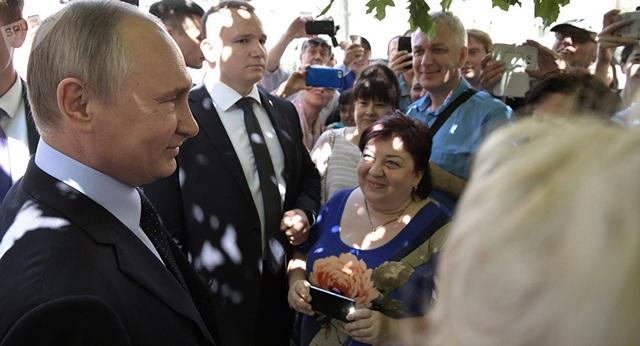 Tổng thống Nga Vladimir Putin nói chuyện với du khách trên đường phố Moscow ngày 20/7. (Ảnh: Sputnik)