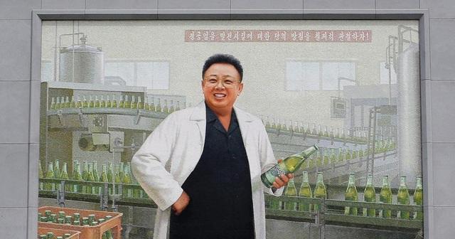Theo Bloomberg, nhà máy bia Taedonggang nằm ở ngoại ô thủ đô Bình Nhưỡng của Triều Tiên được xây dựng theo chỉ thị của cố lãnh đạo Kim Jong-il vào năm 2001 và bắt đầu đi vào hoạt động một năm sau đó. Trong ảnh: Bức tranh vẽ cố lãnh đạo Kim Jong-il mặc áo choàng trắng cầm chai bia Taedonggang được đặt ngay lối vào của nhà máy bia Taedonggang.