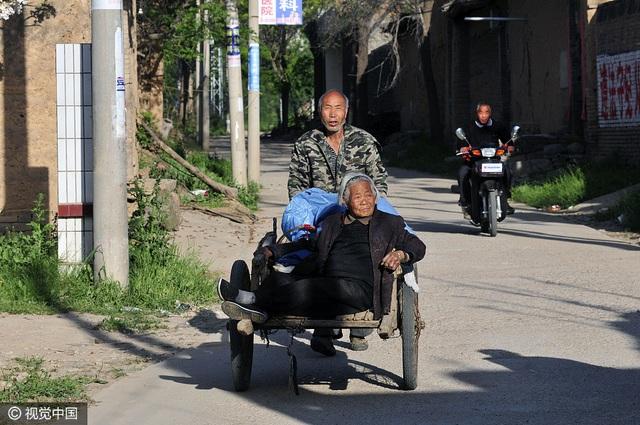 Ông Qi Laolao, 64 tuổi, đưa mẹ về nhà trên chiếc xe kéo tay. Người mẹ 84 tuổi vừa đi bán trứng ngỗng ở chợ. (Ảnh: VCG)