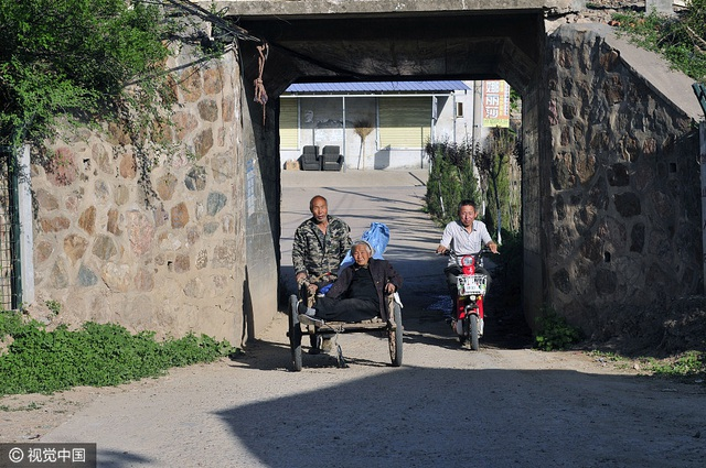 Ông Qi Laolao đưa mẹ từ chợ về nhà bằng chiếc xe kéo tay.