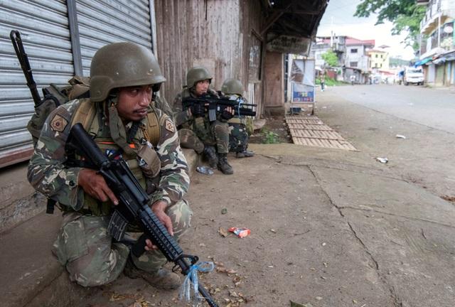 """""""Những người lính của chúng ta đang làm nhiệm vụ của họ. Họ đang dốc hết sức lực và đang tiếp tục nỗ lực để giải phóng Marawi. Hy vọng chiến sự sẽ kết thúc trước ngày thứ hai (12/6)"""", ông Padilla cho biết. Người phát ngôn quân đội tin tưởng rằng quân đội chính phủ sẽ giải phóng toàn bộ thành phố Marawi trước Ngày Độc lập Philippines 12/6. Trong ảnh: Binh lính phục kích phiến quân trên một tuyến đường ở Marawi."""