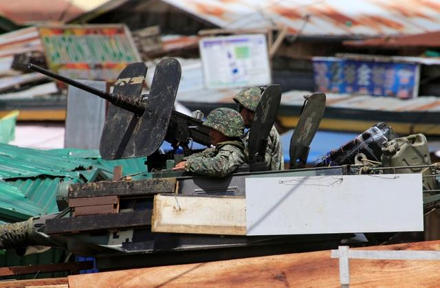 """Cuộc giao tranh giữa quân đội chính phủ Philippines và nhóm phiến quân Maute từng thề trung thành với IS tại thành phố Marawi trên đảo Mindanao, miền nam Philippines tính đến nay đã bước sang ngày thứ 19. Mặc dù còn nhiều khó khăn, song người phát ngôn của quân đội Philippines, Chuẩn tướng Restituto Padilla khẳng định trong cuộc họp báo ngày 9/6 rằng """"số lượng các phần tử khủng bố đang giảm đi từng ngày"""". Trong ảnh: Binh lính Philippines lái xe bọc thép chiến đấu với phiến quân tại Marawi."""