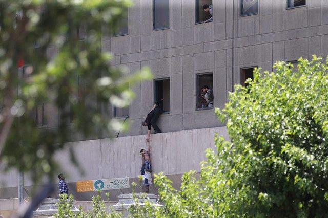 Một em nhỏ được thả qua cửa sổ tòa nhà quốc hội (Ảnh: Fars)
