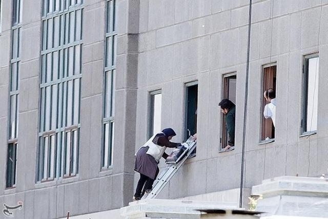 Một phụ nữ treo thang từ tòa nhà quốc hội để ra ngoài
