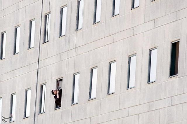 Một thành viên của cảnh sát Iran giương vũ khí bên cửa sổ tòa nhà quốc hội Iran ở thủ đô Tehran ngày 7/6