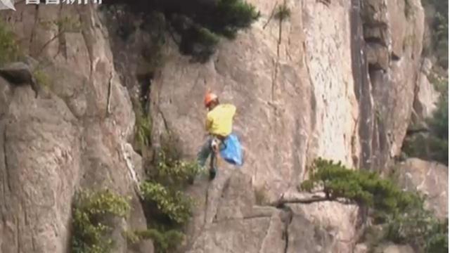 Nhân viên dọn rác thải cheo leo trên vách núi thẳng đứng