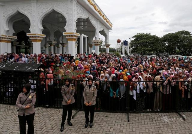 Đám đông theo dõi 2 người đàn ông bị phạt roi (Ảnh: Reuters)