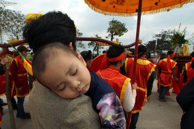 Một em bé ngủ ngon lành trên vai bố đi theo đoàn rước.
