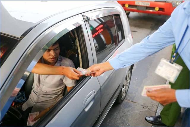 Tài xế cầm hàng xấp tiền lẻ để mua vé, gây khó dễ cho nhân viên trạm BOT.