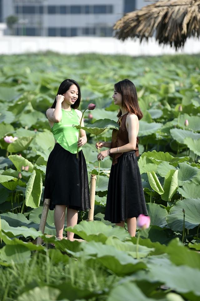 Hai thiếu nữ với trang phục áo yếm mỏng manh chụp ảnh bên hồ sen.