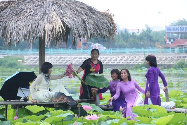 Không chỉ có các bạn trẻ thích chụp ảnh cùng hoa sen, nhiều phụ nữ trung tuổi cũng ra hồ tạo dáng với hoa sen bên áo dài truyền thống để ghi lại những kỷ niệm.