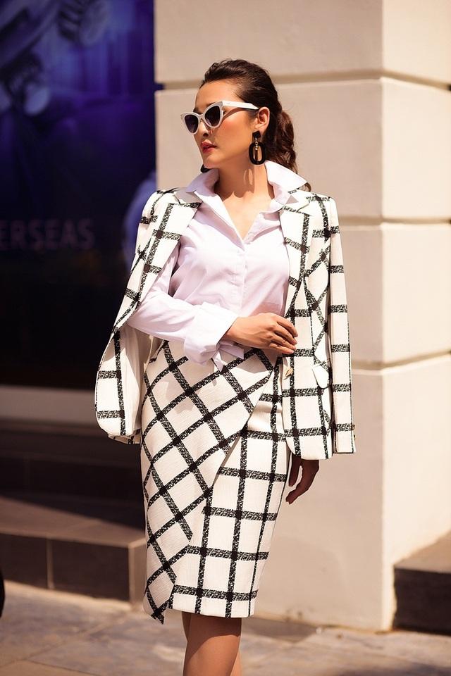 Ngày đầu tuần, nữ MC gợi ý diện áo vest kèm chân váy đồng bộ. Họa tiết kẻ nổi bật trên nền áo sơ mi trắng giúp tạo điểm nhấn sắc sảo cho người mặc. Để thêm sành điệu, cô mix kính mắt mèo và hoa tai to bản.