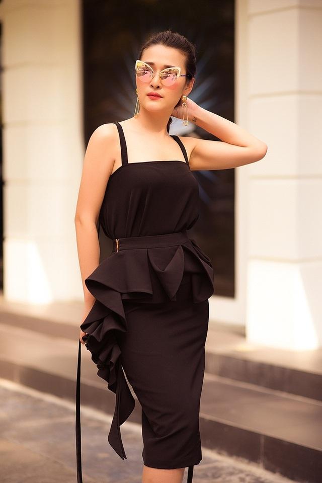 Thứ năm, nữ MC biến thành cô nàng hiện đại với cả bộ cánh màu đen. Áo hai dây kết hợp cùng chân váy bèo nhún dáng ôm, làm tôn lên vòng 3 quyến rũ. Cùng với áo tay chuông, các thiết kế bèo nhún năm nay đang phủ sóng ở đường phố thế giới, được nhiều tín đồ sành sỏi yêu thích.