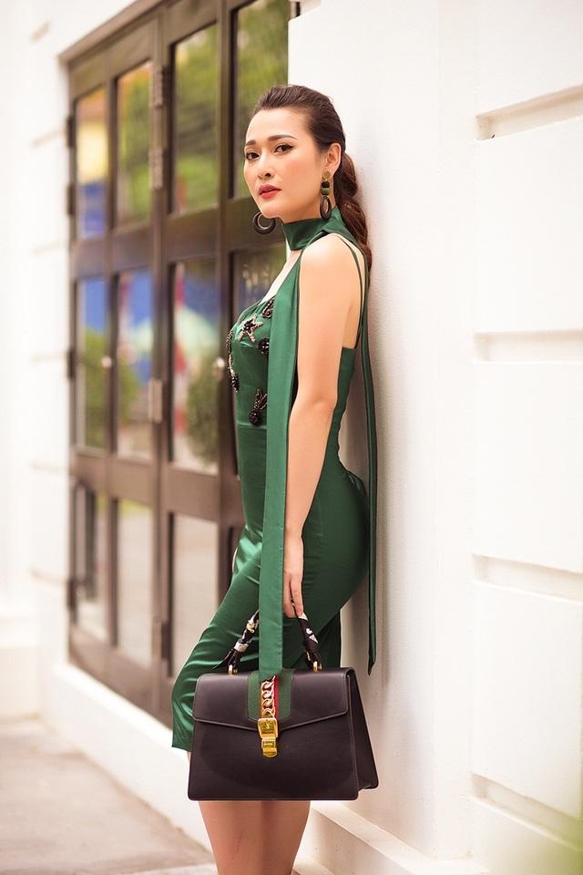 Cô diện váy bó khoét cổ rộng, kết hợp khăn quàng mảnh kiểu choker, xách túi hiệu.