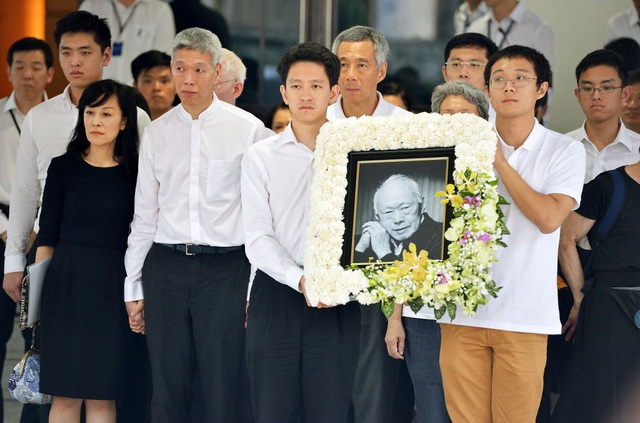 Li Shengwu (quần đen, giữa) và Lý Hồng Nghị cầm di ảnh của ông nội - cố Thủ tướng Lý Quang Diệu trong lễ tang năm 2015. Ông Lý Hiển Dương và Thủ tướng Lý Hiển Long cũng có mặt tại sự kiện. (Ảnh: Straitstimes)