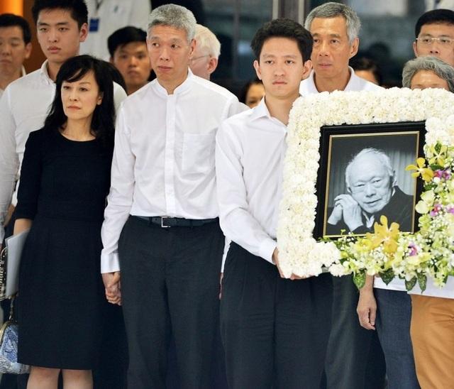 Li Shengwu (phải) cầm di ảnh của ông nội và đứng cạnh ông Lý Hiển Dương trong lễ tang cố Thủ tướng Lý Quang Diệu năm 2015. (Ảnh: Straitstimes)