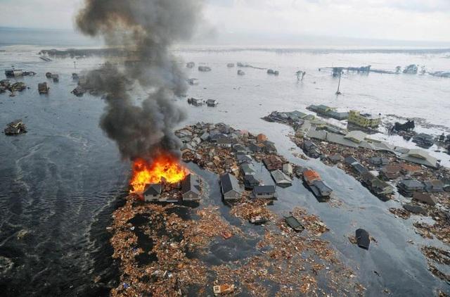 Lửa bốc lên dữ dội từ những ngôi nhà bị sóng thần cuốn ra biển tại thành phố Natori, tỉnh Miyagi.