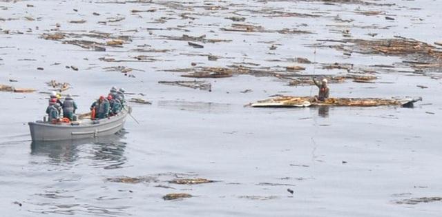 Các thành viên của Lực lượng phòng vệ biển Nhật Bản đi thuyền ra cứu một người đàn ông bị sóng thần cuốn ra biển cách xa bờ 15km.