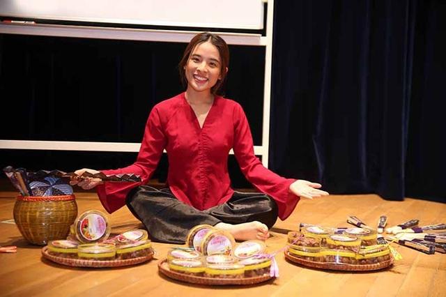 Đại biểu Mai Mai hóa trang thành cụ bà bán nước, vui vẻ chia sẻ những món ô mai truyền thống với người tham dự