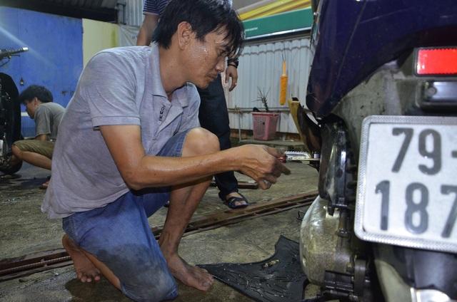 Anh Trung cặm cụi làm công việc sửa xe miễn phí dù chân bị tật, đi lại khó khăn.