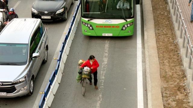 Một người đi xe đạp lạc vào làn buýt nhanh, co cẳng dắt xe chạy khi xe buýt bấm còi phía sau.