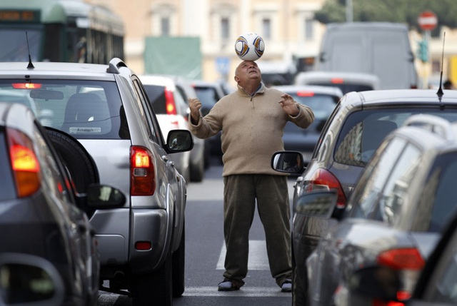 Hàng dài xe ô tô chờ đợi trong cảnh tắc đường ở thành phố Palermo, Italia. Thậm chí, một tài xế phải ra khỏi xe và chơi bóng cho đỡ mỏi chân.