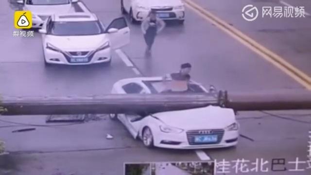 Tài xế may mắn thoát khỏi chiếc xe bị đè bẹp dúm (Ảnh: SCMP)