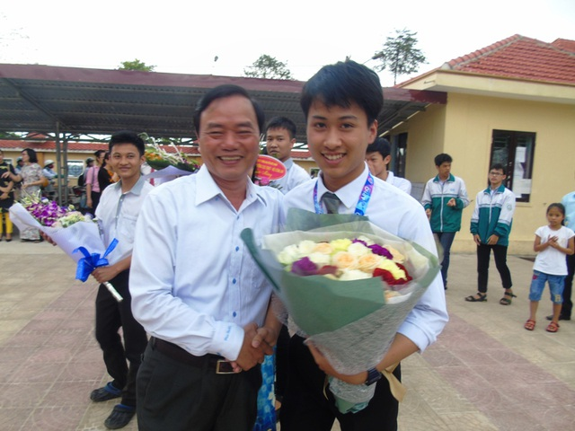 Giám đốc Sở GD-ĐT Quảng Bình Đinh Quý Nhân ra đón và tặng hoa cho chủ nhân của tấm HCB Olympic Vật lý châu Á 2017