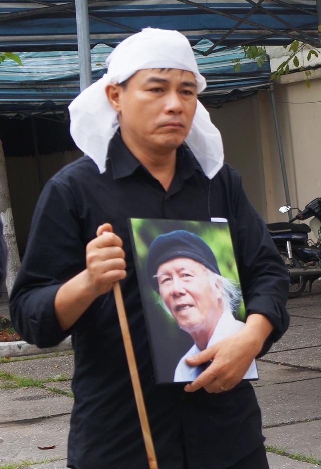 Anh Doãn Thi, con trai lớn của nhà thơ Thanh Tùng cầm di ảnh của cha với gương mặt buồn bã vì sự mất mát quá lớn của gia đình.