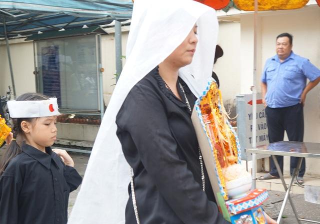 Chị Lan Hương, con gái của nhà thơ cầm bài vị của cha với ánh mắt đượm buồn, trong suốt những ngày diễn ra tang lễ, chị luôn không cầm được nước mắt của mình.