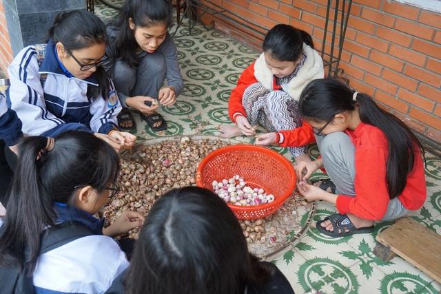 Các em nhỏ cùng các tình nguyện viên bóc hành chuẩn bị nhân gói bánh chưng.