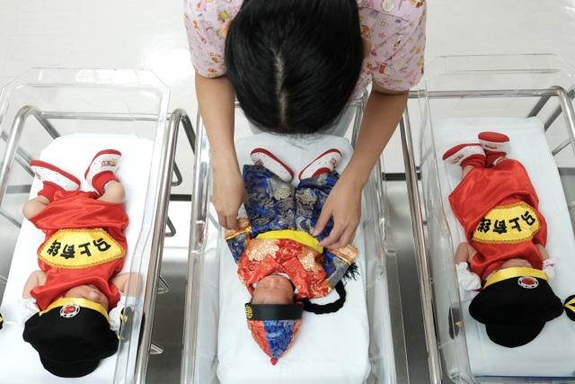 Một nữ y tá mặc quần áo truyền thống của người Trung Quốc cho các bé sơ sinh nhân dịp năm mới tại phòng hậu sinh ở bệnh viện Paolo Chockchai, Bangkok, Thái Lan. (Ảnh: Reuters)