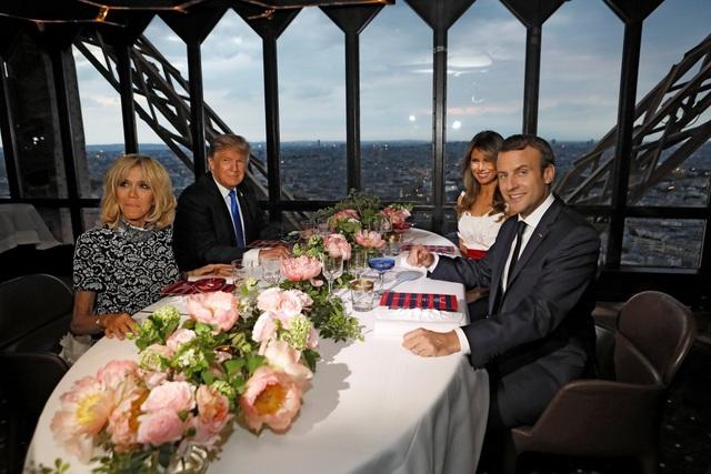 Trong bữa tiệc, ông Trump được nhìn thấy ngồi cạnh Đệ nhất phu nhân Pháp Brigitte, trong khi Tổng thống Macron ngồi cạnh Đệ nhất phu nhân Mỹ Melania. (Ảnh: Reuters)