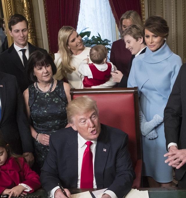Barron Trump (thứ hai từ phải sang) chơi đùa cùng cháu trai Theo khi bố, Tổng thống Donald Trump, đang ký văn bản đầu tiên (Ảnh: AP)