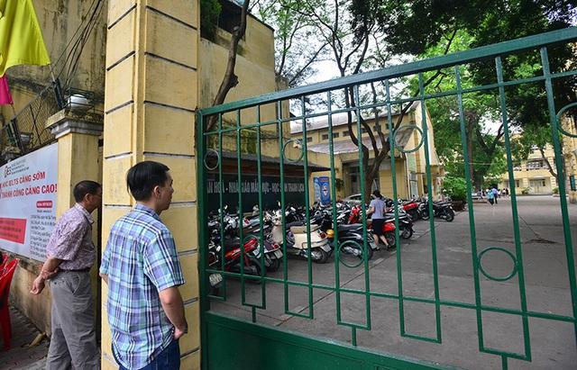 8h, giờ thi chính thức bắt đầu. Các phụ huynh đứng ngoài cổng trường đợi con.