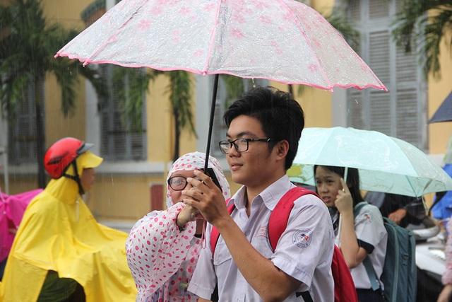 Dưới cơn mưa, nhiều thí sinh gương mặt hớn hở chấp nhận ướt mưa về nhà.