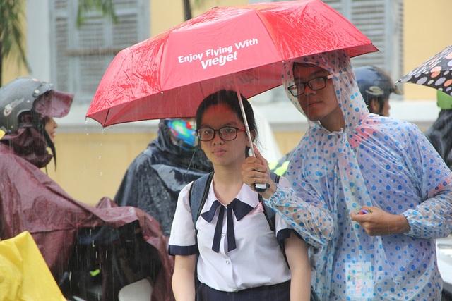Lực lượng sinh viên tình nguyện đội mưa che dù cho thí sinh tạo nên những hình ảnh đẹp của mùa thi năm nay