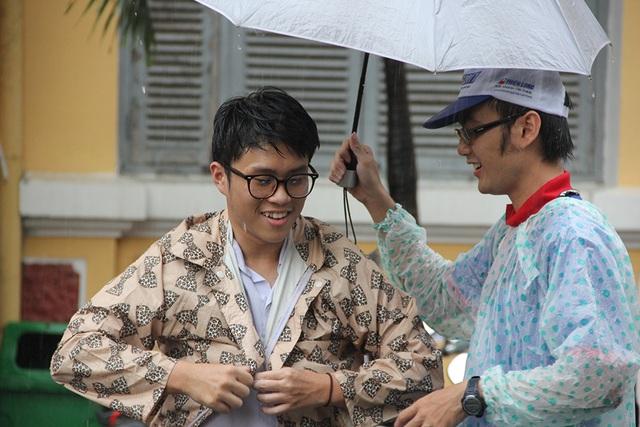 Một thí sinh được sinh viên tình nguyện che ô để mặc áo mưa