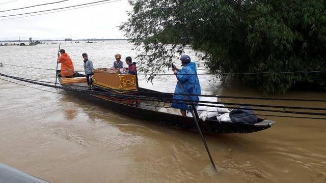 Người thân dùng ghe chèo trên cánh đồng ngập nước đưa thi thể nạn nhân về nhà